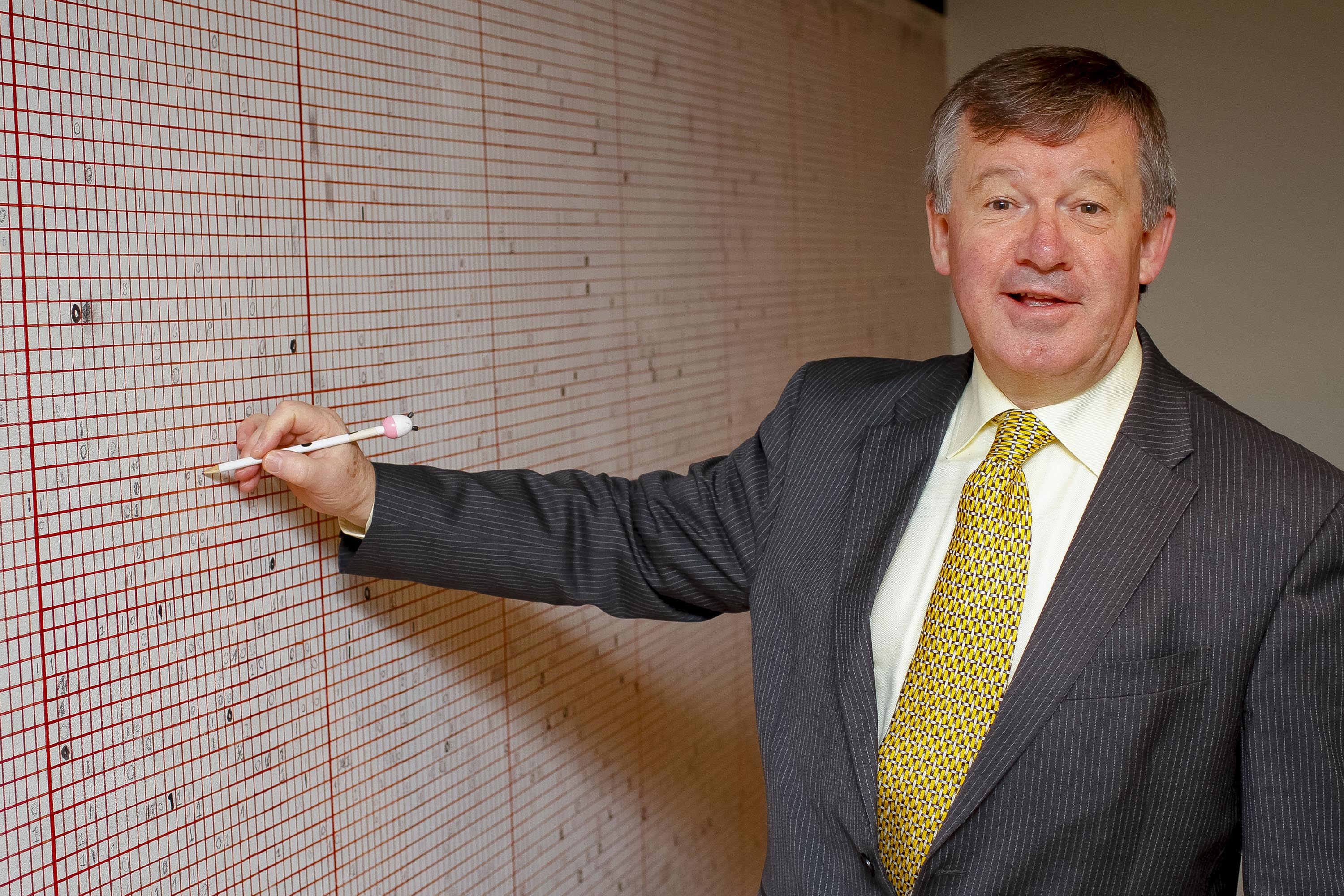 President Michael Murphy, UCC, adds his mark to the Live Statistics Wall at the Glucksman Gallery.